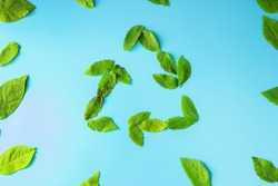recycable sign with green leaves on blue background