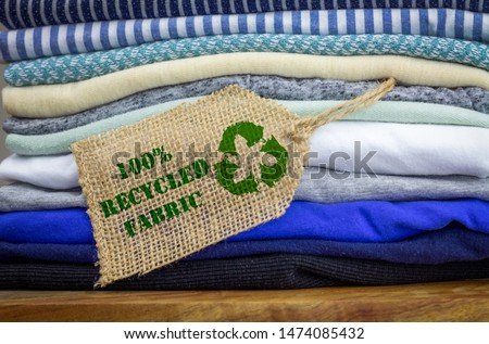 Recycle clothes icon on fabric label with 100 percent Recycled text, concept illustration reuse, recycle clothes and textiles to reduce waste