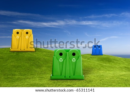 Recycle containers for glass, metal, plastic and paper waste placed on a green meadow lansdscape