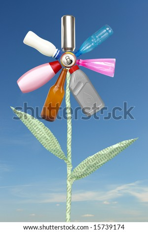 Recycle flower created from beer can, plastic and glass bottles and waste paper stem spelling reduce-reuse-recycle over blue sky