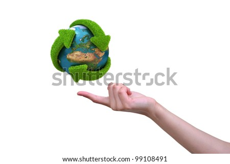 Recycle globe with green arrows covered with grass presented on female finger