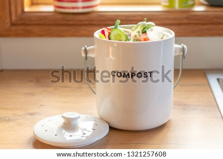 Recycle kitchen waste, sustainable living food waste recycling, food waste compost pot containing kitchen waste on kitchen counter top