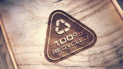 Recycle logo engraved on wood background.
