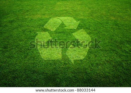 Recycle symbol on a fresh green grass, environmental concept image.
