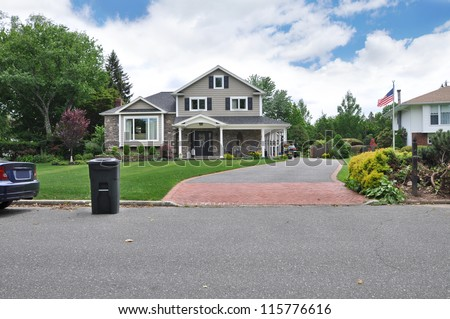 Recycle Trash Container on street curb of Large Cape Cod Style Suburban Neighborhood Home with brick and blacktop driveway