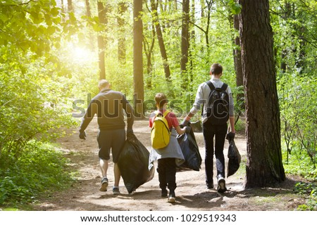 Recycle waste litter rubbish garbage trash junk clean training. Nature cleaning, volunteer ecology green concept. Young men and boys pick up spring forest at sunset . Environment plastic pollution #1029519343