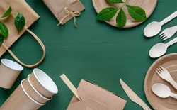 Recycled Eco-friendly disposable tableware made of paper on a green background. Wooden spoons, fork, knive, with paper cups, box, bamboo chopstic.