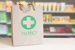 Recycled paper bag with a green Pharmacy logo in a drugstore. Empty copy space for Editor's content..