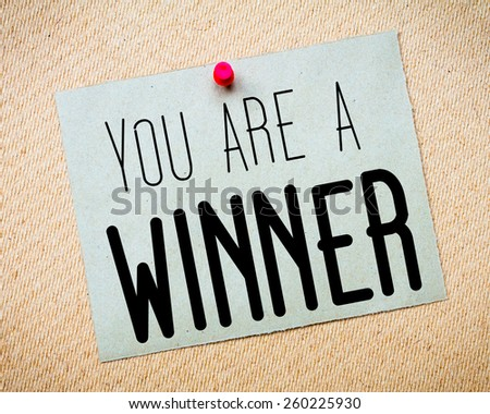 Recycled paper note pinned on cork board.  You are a winner Message. Concept Image