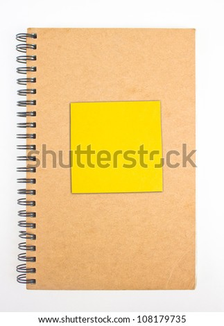 Recycled paper notebook front cover with yellow sticky note.