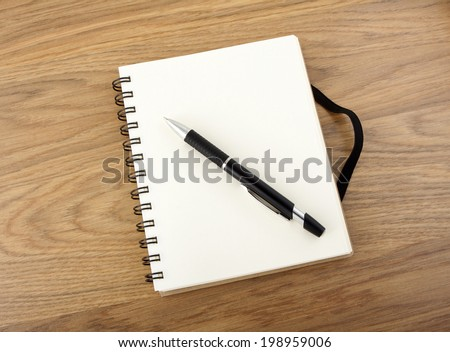 Recycled paper notebook with black elastic band and pen on a table