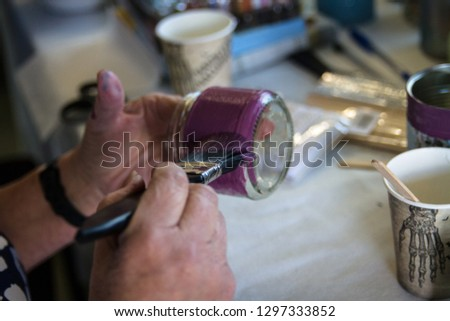 Recycling a glass jar into a decorated plant pot. Hands shown painting the jar with chalk paint by a crafting table with crafting supplies on.  Crafting, recycling, gardening. #1297333852