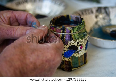 Recycling a glass jar into a decorated plant pot. Hands tying string around the jar neck on crafting table with crafting supplies on.  Crafting, recycling, gardening. #1297333828