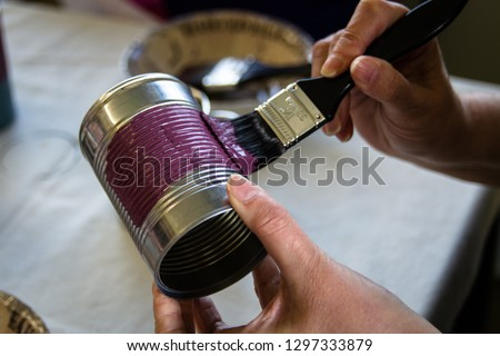 Recycling a tin can into a decorated plant pot. Hands shown painting the pot with chalk paint by a crafting table with crafting supplies on.  Crafting, recycling, gardening. #1297333879