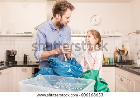 Recycling and ecology - happy caucasian family (father and daughter) sorting (segregating) household waste in the kitchen. Lifestyle - ecological education and awareness concept. #606168653