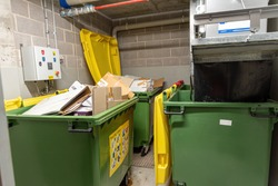 recycling bins and garbage chute disposal room in apartment buil