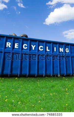 Recycling business and container with car tires on green fresh grass over blue sky
