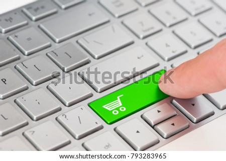 8e3d4d06624 Recycling concept  A finger press a green key with Shopping cart icon symbol  on laptop