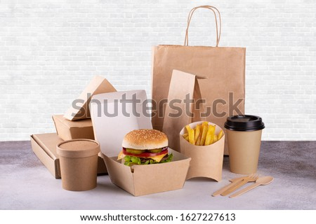 Recycling concept. Delivery food background. Fast food eco packaging with tasty hamburger, french fries, paper coffee cup and soup Foto stock ©