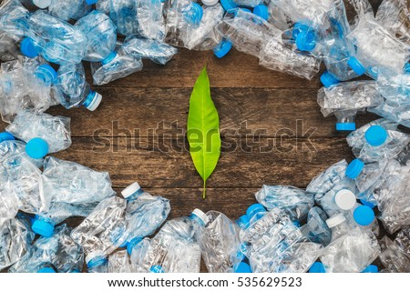 Recycling concept. Green leaves on a wooden background around the transparent plastic bottles. The problem of ecology, environmental pollution. #535629523