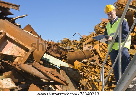 Recycling expert, standing on a metal staircase in front of a steel scrap heap