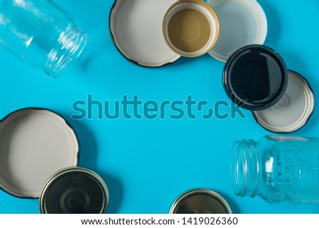 Recycling glass jar lids; Reuse of single use items; Zero no waste recycle program campaigns; Recyclable concept on blank empty copyspace, text room space for copy on horizontal light blue background. #1419026360