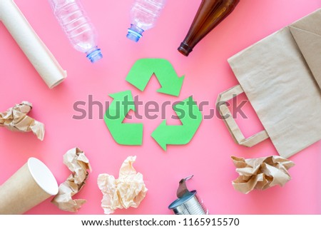 Recycling. Green recycle eco symbol. Recycled arrows sign near matherials for recycle and reuse on pink background top view