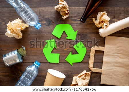 Recycling. Green recycle eco symbol. Recycled arrows sign near matherials for recycle and reuse on dark wooden background top view