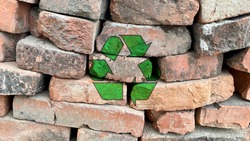 Recycling icon on a pile of red bricks from a construction site, sort and recycle waste building materials, be responsible and protect ecological environment, environmental protection symbol texture