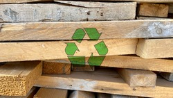 Recycling icon on waste wood planks from construction site, sort and reuse abandoned materials, sustainable and responsible development texture, creative environmental protection symbol background