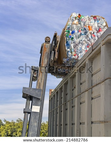 Recycling plastic bottles. Industrial machine crane with stack of empty crushed plastic drinking containers in cardboard box and large metal dumpster. Green bushes, blue sky and clouds background.