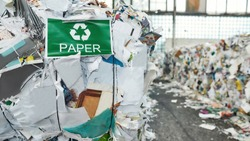 Recycling sign and green arrows on banner hanging on waste paper pile inside rubbish station, widescreen. Garbage sorting and recycling concept