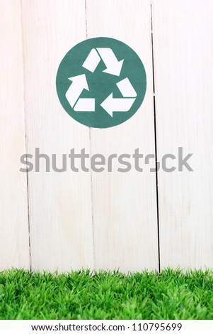 Recycling sign on wooden background