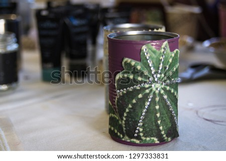Recycling tin cans into decorated plant pots. Cans shown without plants sitting on crafting table with crafting supplies in the background.  Crafting, recycling, gardening. #1297333831