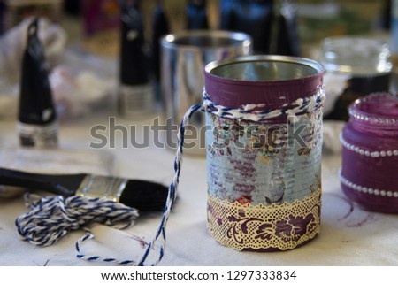 Recycling tin cans into decorated plant pots. Cans shown without plants sitting on crafting table with crafting supplies in the background.  Crafting, recycling, gardening. #1297333834