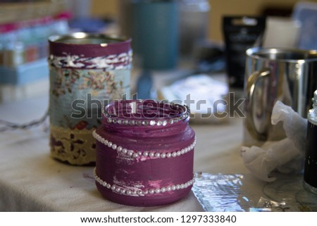 Recycling tin cans into decorated plant pots. Cans shown without plants sitting on crafting table with crafting supplies in the background.  Crafting, recycling, gardening. #1297333840