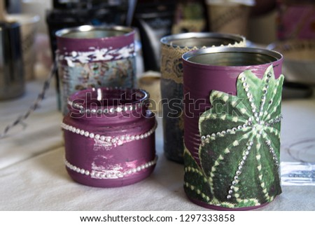 Recycling tin cans into decorated plant pots. Cans shown without plants sitting on crafting table.  Crafting, recycling, gardening.