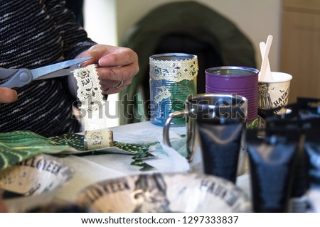 Recycling tin cans into decorated plant pots. Person cutting lace beside crafting table with crafting supplies on.  Crafting, recycling, gardening. #1297333837