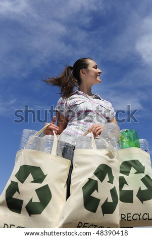 recycling: woman holding bag with plastic bottles against blue sky