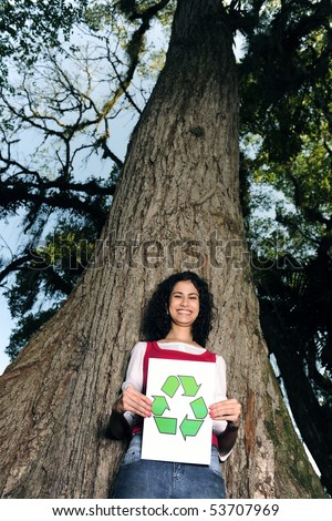 recycling:woman in front of a tree holding a recycle sign smiling