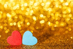Red abd blue little decorative hearts against gold yellow sparkle glitter background with amazing bokeh lights. Love or romantic Valentine day concept. Holiday background