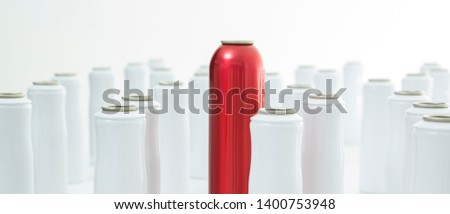 red aerosol can between white aerosol cans on white background