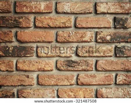 Red aged brick wall wallpaper closeup.