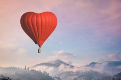 Red air balloon heart shape against blue and pink pastel sky in a sunny bright morning. Foggy mountains in the background. Romantic postcard background on Valentine's Day. Travel and recreation theme