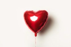 red air balloon in the form of a heart on a white background