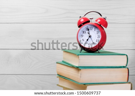 Red alarm clock among books and textbooks on a light wooden background, educational concept, back to school