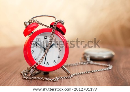 Red alarm clock in chain with an old pocket watch on wooden background or desk. Clock wrapped in chains. Concept of time constraints, deadline, time management, lack or shortage of time. Stock photo ©