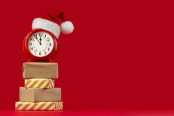 Red alarm clock in Santa Claus hat on gift boxes. Red background. Concept of coming Christmas and New Year, holiday sales. Space for text