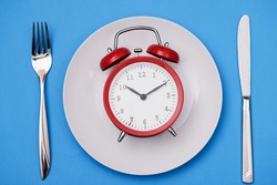 Red alarm clock lies on plate next to fork and knife