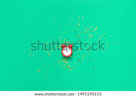 Red alarm clock on green background with golden glitter stars. 2020 new year or chritmas eve card